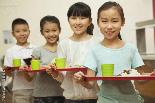 Row of students standing in line in school cafeteria