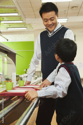 Teacher and student talking in school cafeteria