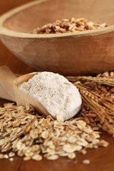 Wholegrain flour on wooden spoons, oats and corn