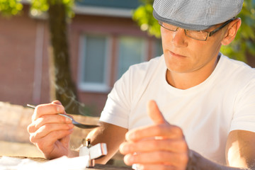 Middle-aged man heating soluble heroin outdoors
