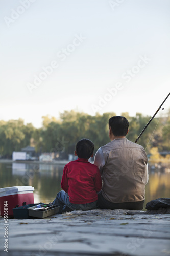 Grandfather and grandson sitting and fishing at a lake