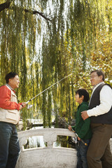 Multi-generational men fishing at lake