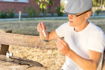 Man filling a syringe with soluble crack cocaine