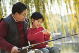 Grandfather and grandson putting lure on fishing line