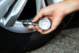 Hand holding pressure gauge for car tyre pressure measurement