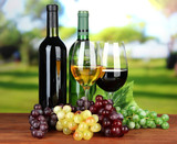 Wine bottles and glasses of wine on bright background