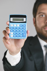 Portrait of a young businessman showing a zero on calculator.