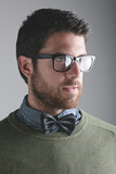 Stylish young man wearing bowtie and glasses on grey Background.