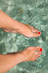 Close up of feet with red nail on sea background.