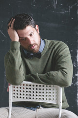 Stressed stylish teacher man  in front a blackboard.