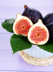 Ripe figs in bowl on wooden table close-up