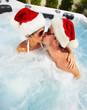Happy Christmas santa couple in jacuzzi.