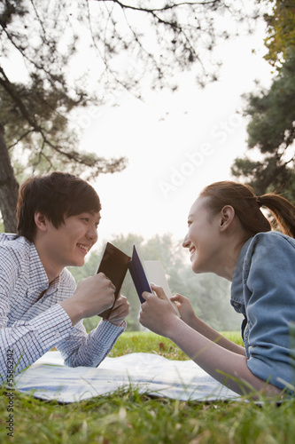 Teenage couple reading books in the park