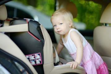 Toddler girl getting into a car seat
