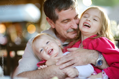 Grandfather hugging his grandchildren