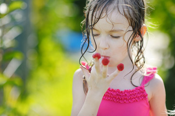 Adorable little girl eating raspberries