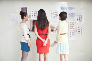 Businesswomen Looking At Wall of Ideas