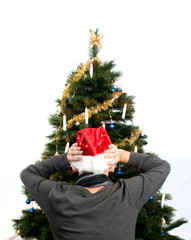 Rear view of man worring in front of christmas tree