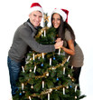 Couple standing behind decorated christmas tree