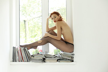 Naked Auburn Woman in Torn Tights on Magazines over Window