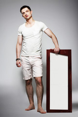 Full Length of Young Barefoot Man in White Shorts with Plackard