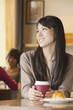 Beautiful young woman sitting at a coffee shop, looking away