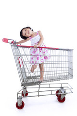 Asian girl inside shopping trolley - isolated
