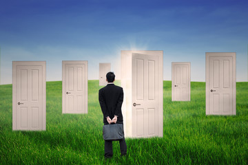 Businessman standing in front of opportunity door