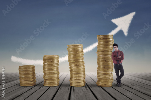Confident businessman standing next to gold coins chart