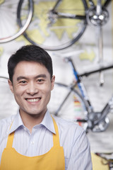 Portrait of young male mechanic in bicycle store, Beijing