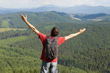 Happy man with hands up  on mountain
