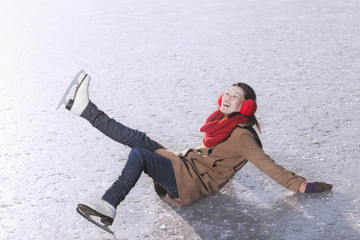 Young Woman Falling While Ice Skating