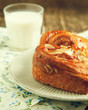 Almond Danish pastry on plate with glass of milk