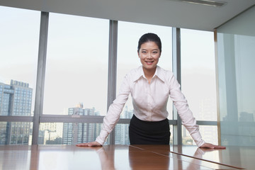 Young businesswoman leaning on table in office, portrait