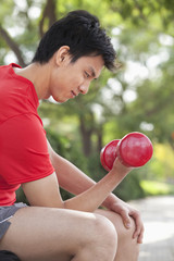 Young Man exercising with Dumbbell