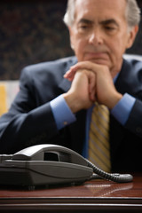 Pensive businessman with telephone