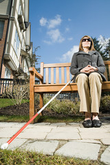 Blind woman sitting on a bench