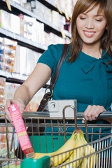 Young woman putting a packet in a shopping trolley