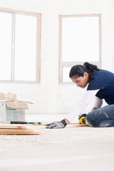 A female builder measuring a plank of wood