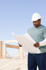 A builder holding a blueprint