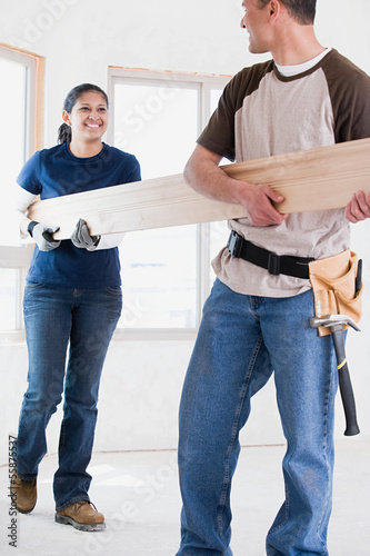 A couple holding a plank of wood