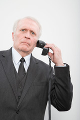 A confused businessman using a telephone