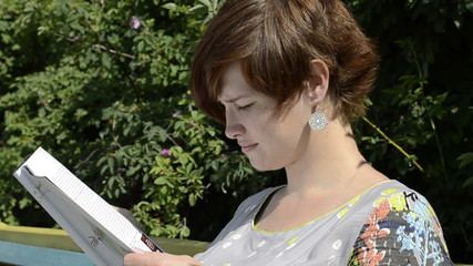 Pregnant woman reading magazine in summer day