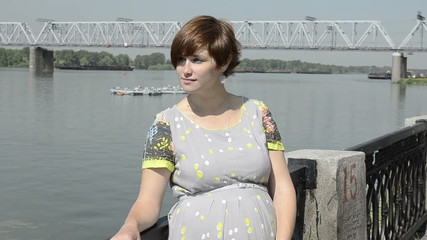 pregnant beautiful young woman by embankment, near the river