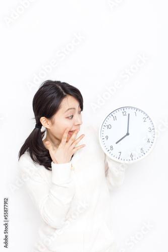 時計を見て驚く女性