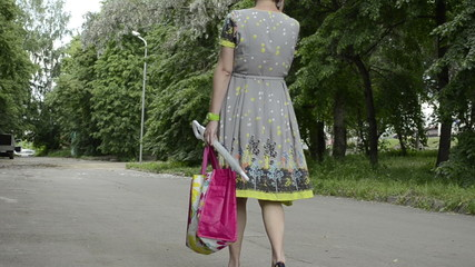 Young pregnant woman is walking in a park. back view
