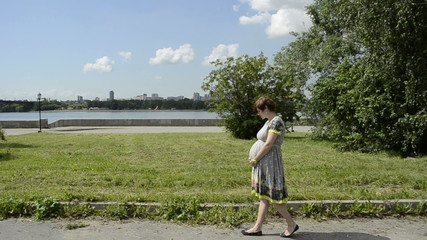 Young pregnant woman walking in a park next to a river