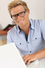Portrait of smiling attractive young man in office