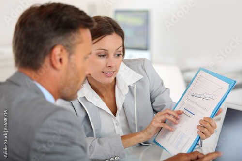 Leinwanddruck Bild Young woman presenting business plan to financial investor
