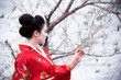 Asian style portrait of a woman with a little red flower